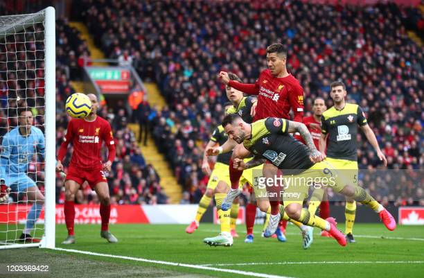 Danny Ings of Southampton heads the ball while under pressure from Roberto Firmino of Liverpool during the Premier League match between Liverpool FC...