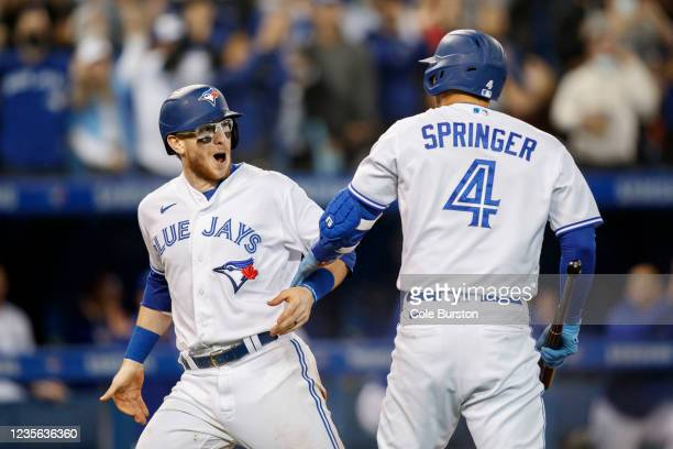 Danny Jansen and George Springer of the Toronto Blue Jays celebrate Jansens run off a Cavan Biggio double in the sixth inning of their MLB game...