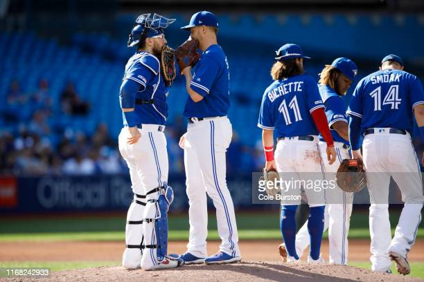 Danny Jansen of the Toronto Blue Jays and Justin Shafer have a meeting on the mound as he enters the game in the eighth inning of their MLB game...