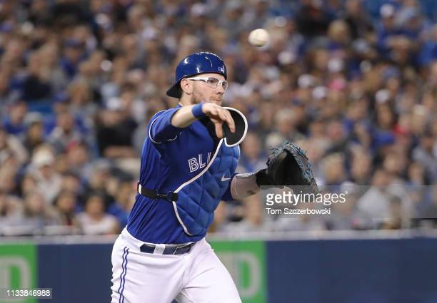 Danny Jansen of the Toronto Blue Jays fields a soft grounder in front of home plate and throws out the baserunner in the second inning during MLB...