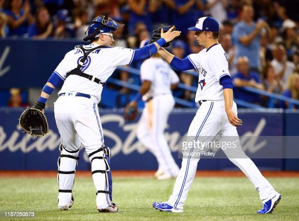 Danny Jansen of the Toronto Blue Jays high fives pitcher Ryan Borucki in the fourth inning during a MLB game against the Cleveland Indians at Rogers...