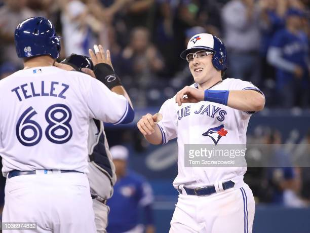 Danny Jansen of the Toronto Blue Jays is congratulated by Rowdy Tellez after hitting a threerun home run in the ninth inning during MLB game action...