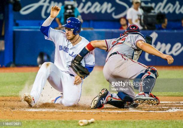 Danny Jansen of the Toronto Blue Jays is safe at home plate against Tyler Flowers of the Atlanta Braves in the sixth inning at the Rogers Centre on...