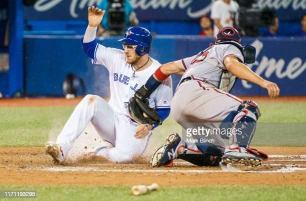 Danny Jansen of the Toronto Blue Jays is safe at home plate on a hit past Tyler Flowers of the Atlanta Braves in the sixth inning during their MLB...