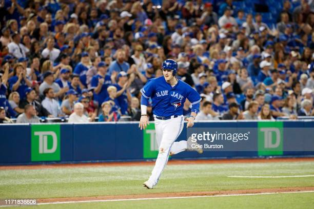 Danny Jansen of the Toronto Blue Jays runs into home plate to score off Richard Urena of the Toronto Blue Jays' double during the seventh inning of...