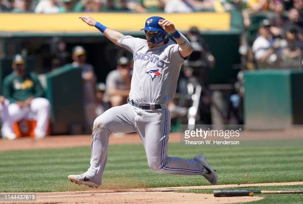 Danny Jansen of the Toronto Blue Jays slides at home plate against the Oakland Athletics in the top of the third inning of a Major League Baseball...