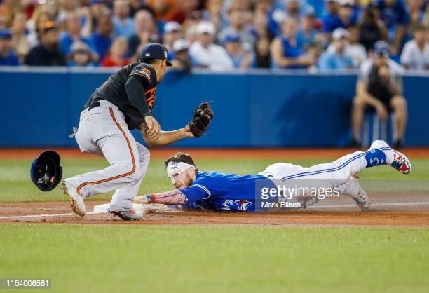 Danny Jansen of the Toronto Blue Jays slides safely into third for a triple against Rio Ruiz of the Baltimore Orioles in the second inning during...
