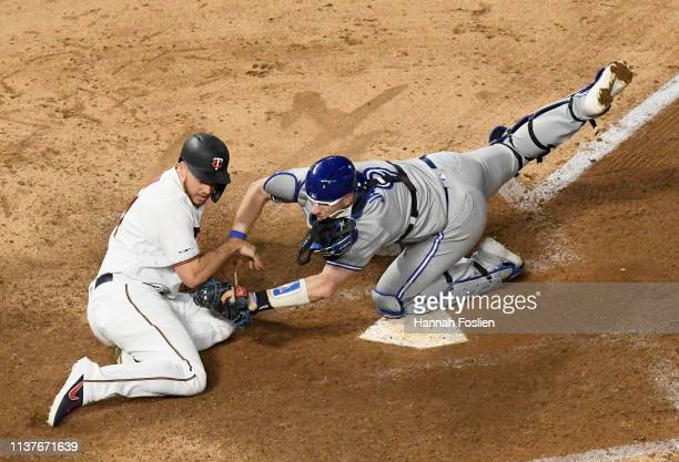 Danny Jansen of the Toronto Blue Jays tags out CJ Cron of the Minnesota Twins at home plate to end the game on April 16 2019 at Target Field in...