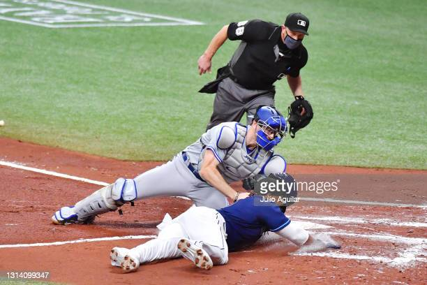 Danny Jansen of the Toronto Blue Jays tags Yandy Diaz of the Tampa Bay Rays out at home in the first inning at Tropicana Field on April 23, 2021 in...