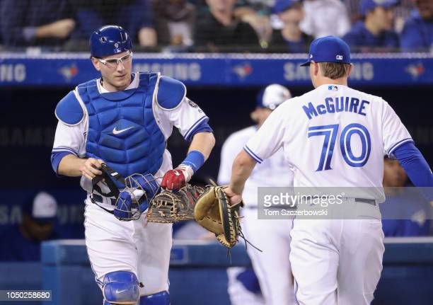 Danny Jansen of the Toronto Blue Jays taps gloves with Reese McGuire who helped him warm up the pitcher before the start of the next inning during...