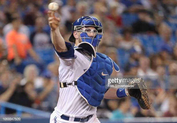 Danny Jansen of the Toronto Blue Jays throws the ball to first base to complete the strikeout in the fifth inning during MLB game action against the...