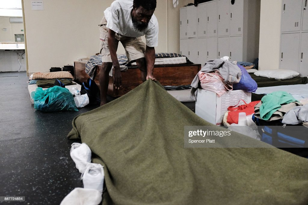 Danny Jeffrey, A displaced resident from the island of Barbuda, makes his bed inside a shelter at a cricket stadium on December 7, 2017 in St John's, Antiqua. Barbuda, which covers only 62 square miles, was nearly leveled when Hurricane Irma made landfall with 185mph winds on the night of September 6. Only two days later, fearing Barbuda would be hit again by Hurricane Jose, the prime minister ordered an evacuation of all 1,800 residents of the island. Most are now still in shelters scattered around Barbuda's much larger sister island Antigua.