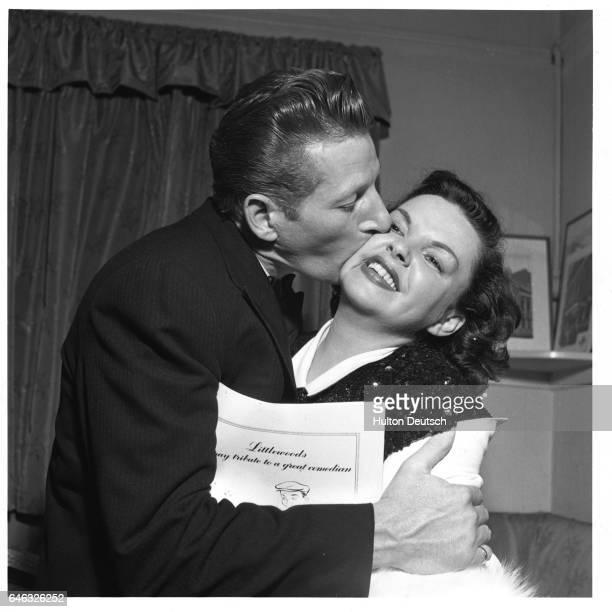 Danny Kaye plants a big kiss on Judy Garland's cheek following their appearances in the AllStar Midnight Sid Field Tribute at the London Palladium...