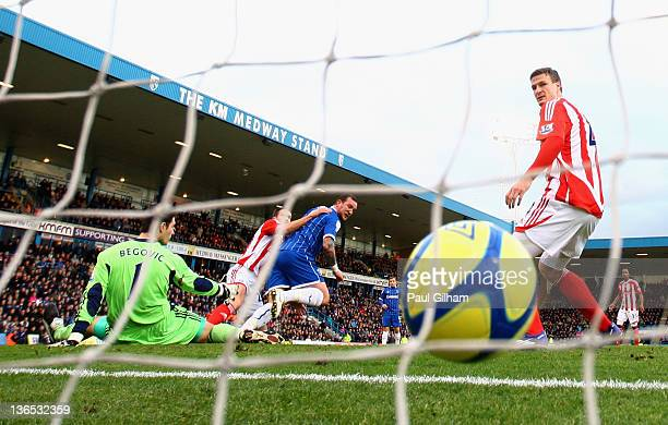 Danny Kedwell of Gillingham scores the opening goal past Asmir Begovic of Stoke City as teammate Robert Huth looks on during the FA Cup Third Round...