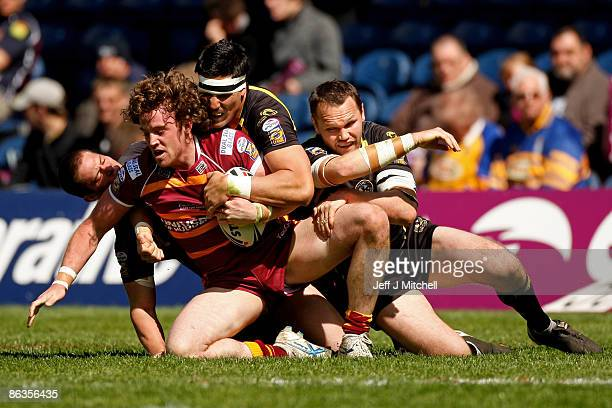 Danny Kirmond of Huddersfield is hauled down by the Crusaders defence during the Super League Magic Weekend match between Huddersfield Giants and...