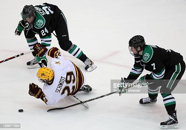 Danny Kristo of North Dakota hooks Nate Schmidt of Minnesota as Jordan Schmaltz looks for the loose puck January 19 2013 at Mariucci Arena in...