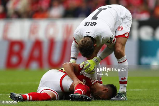 Danny Latza of Mainz lies in pain on the pitch while goalkeeper Rene Adler of Mainz checks on him during the Bundesliga match between 1 FSV Mainz 05...