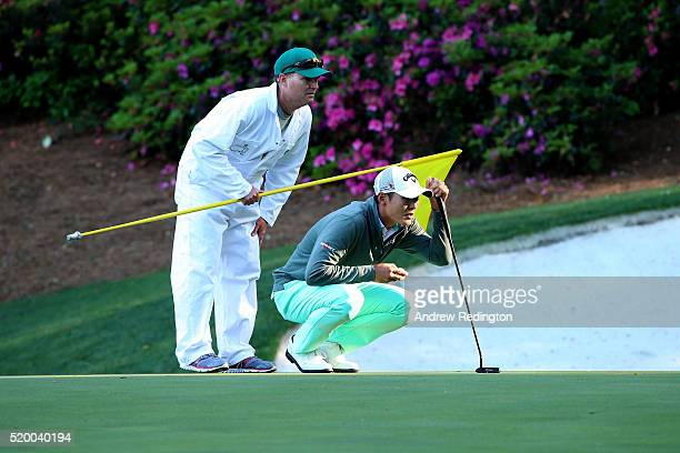 Danny Lee of New Zealand and caddie Mike Hartford line up a putt on the 13th green during the third round of the 2016 Masters Tournament at Augusta...