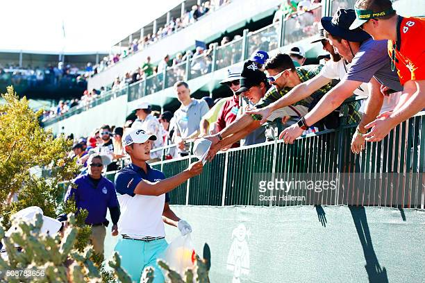 Danny Lee of New Zealand hands caps to golf fans on the 16th hole during the third round of the Waste Management Phoenix Open at TPC Scottsdale on...
