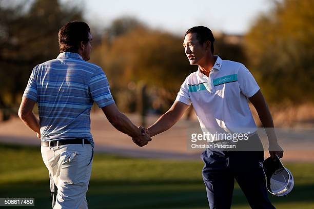 Danny Lee of New Zealand shakes hands with Keegan Bradley after finishing their round on the ninth hole during the second round of the Waste...