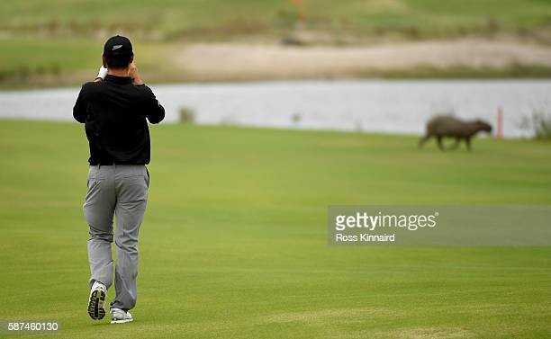 Danny Lee of New Zealand takes a photo of a capybara on the 5th hole during a practice round at Olympic Golf Course on August 8 2016 in Rio de...