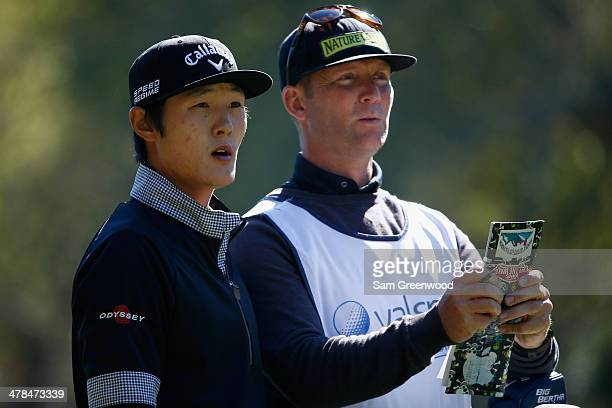 Danny Lee of South Korea assesses a shot with his caddy on the 17th hole during the first round of the Valspar Championship at Innisbrook Resort and...