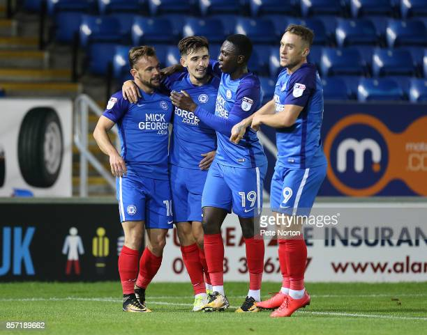 Danny Lloyd of Peterborough United celebrates with team mates after scoring his sides first goal during the Checkatrade Trophy match between...