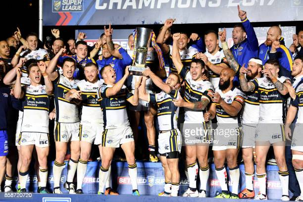 Danny McGuire and Rob Burrow of Leeds Rhinos lift the trophy with their teammates at the end of the Betfred Super League Grand Final match between...