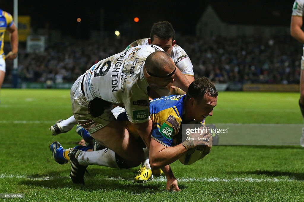 Danny McGuire of Leeds Rhinos dives past a tackle from Danny Houghton and Shannon McDonnell of Hull FC to score his try during the Stobart Super League match between Leeds Rhinos and Hull FC at Headingley Carnegie Stadium on February 1, 2013 in Leeds, England.
