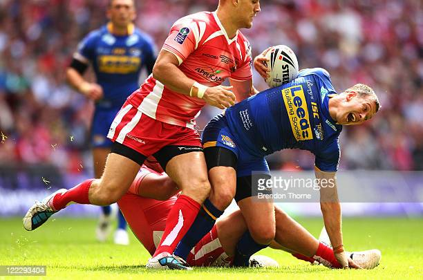 Danny McGuire of Leeds Rhinos is tackled by the Wigan Warriors defence during the Carnegie Challenge Cup Final between Leeds Rhinos and Wigan...