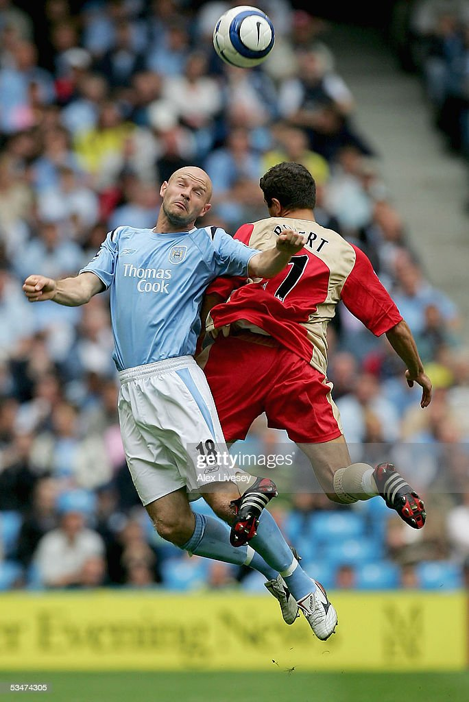 Danny Mills of Manchester City beats Laurent Robert of Portsmouth to the ball during the Barclays Premiership match between Manchester City and Portsmouth at the City of Manchester Stadium on August 27, 2005 in Manchester, England.