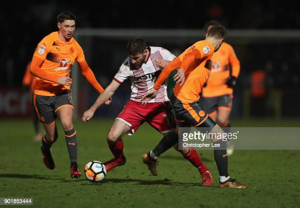 Danny Newton of Stevenage weaves his way past George Evans and Chris Gunter of Reading during The Emirates FA Cup Third Round match between Stevenage...