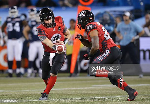 Danny O'Brien of the Ottawa Redblacks hands the ball off to Jeremiah Johnson during CFL game action against the Toronto Argonauts on November 7 2014...