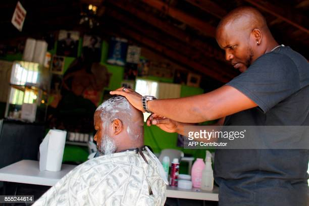 Danny Rivera shaves Carlos Quinones in the aftermath of Hurricane Maria in Loiza Puerto Rico September 28 2017 The US island territory working...