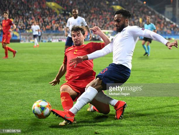 Danny Rose of England is chalenged by Filip Stojkovic of Montenegro during the 2020 UEFA European Championships Group A qualifying match between...