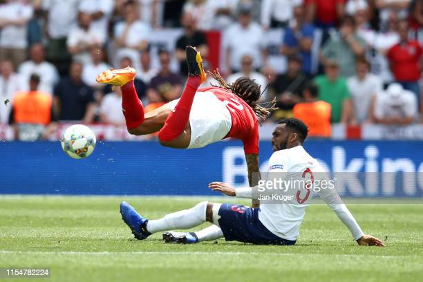 Danny Rose of England tackles Kevin Mbabu of Switzerland during the UEFA Nations League Third Place Playoff match between Switzerland and England at...
