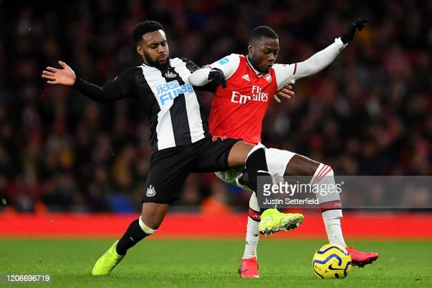 Danny Rose of Newcastle United tackles Nicolas Pepe of Arsenal during the Premier League match between Arsenal FC and Newcastle United at Emirates...