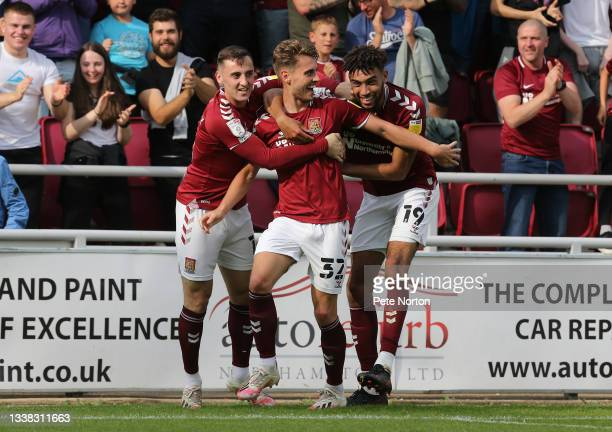 Danny Rose of Northampton Town is congratulated by team mates Dylan Connolly and Kion Etete after scoring his sides first goal during the Sky Bet...