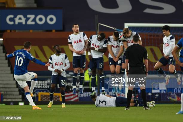 Danny Rose of Tottenham Hotspur lies down under the Tottenham Hotspur wall as Eric Dier and Harry Kane block a free-kick from Gylfi Sigurdsson of...