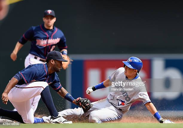 Danny Santana of the Minnesota Twins catches Munenori Kawasaki of the Toronto Blue Jays stealing second base during the eighth inning of the game on...