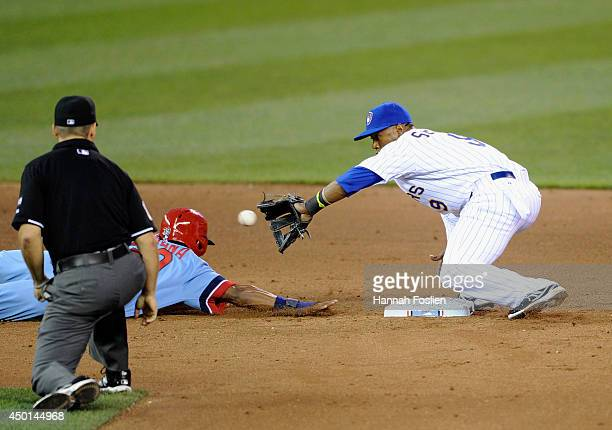 Danny Santana of the Minnesota Twins slides back safely to second base as Jean Segura of the Milwaukee Brewers fields the ball and umpire Mark Wegner...