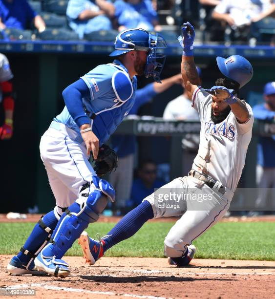 Danny Santana of the Texas Rangers scores past Cam Gallagher of the Kansas City Royals on a Willie Calhoun tworun single in the fifth inning at...