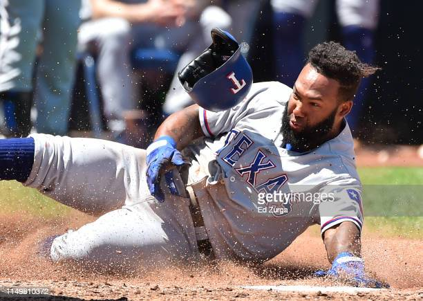Danny Santana of the Texas Rangers slides into home to score on a Willie Calhoun two-run single in the fifth inning at Kauffman Stadium on May 16,...