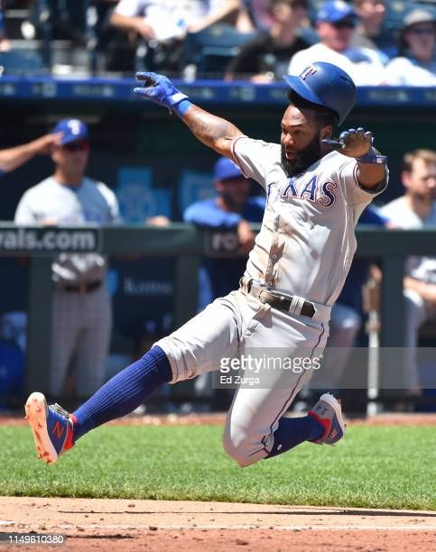 Danny Santana of the Texas Rangers slides into home to score on a Willie Calhoun tworun single in the fifth inning at Kauffman Stadium on May 16 2019...