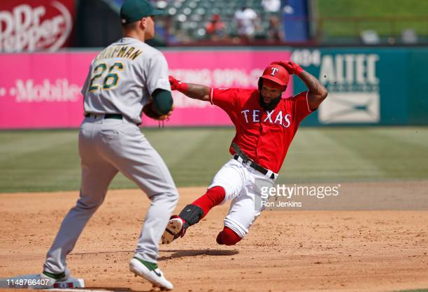 Danny Santana of the Texas Rangers slides into third base ahead of the throw to Matt Chapman of the Oakland Athletics on a triple in the third inning...