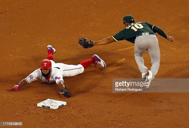 Danny Santana of the Texas Rangers steals second ahead of the tag by Marcus Semien of the Oakland Athletics in the second inning at Globe Life Park...