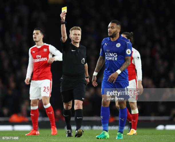 Danny Simpson of Leicester City is shown a yellow card by match referee Mike Jones during the Premier League match between Arsenal and Leicester City...