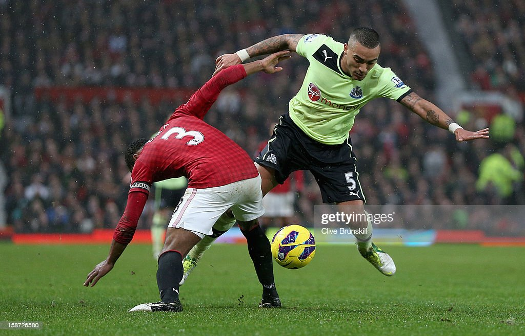 Danny Simpson of Newcastle United is tackled by Patrice Evra of Manchester United during the Barclays Premier League match between Manchester United and Newcastle United at Old Trafford December 26, 2012 in Manchester, England.