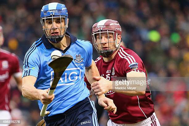 Danny Sutcliffe of Dublin carries the sliotar with pressure from Andy Smith of Galway during the AIG Fenway Hurling Classic and Irish Festival at...