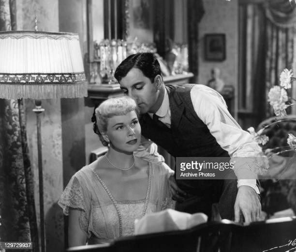 Danny Thomas leans over to kiss Doris Day as she's at the piano in a scene from the film 'I'll See You In My Dreams' 1951
